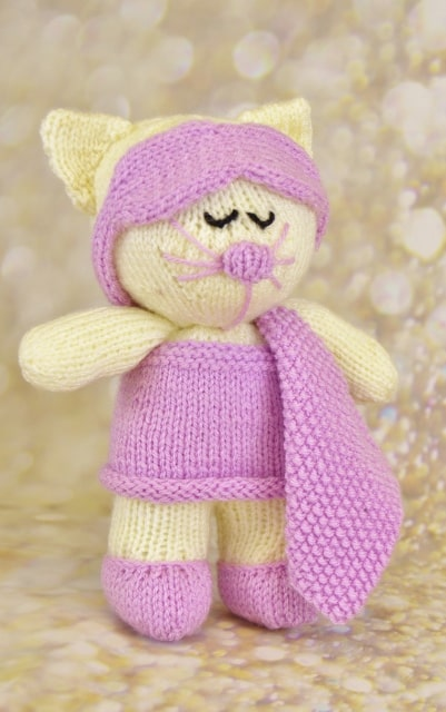 cat ready for bed in cream and pink with nightie slippers and eyemask knitting pattern